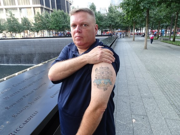 """David Brink shows his tattoo honoring the memory of those First Responders who died on 9/11. The tattoo says, """"In Memory of Our Fallen Brothers 9-11-2001 W.W. [Walter Weaver] - J.D. [Jerome Dominguez]"""" - Photo by Nehemia Gordon"""