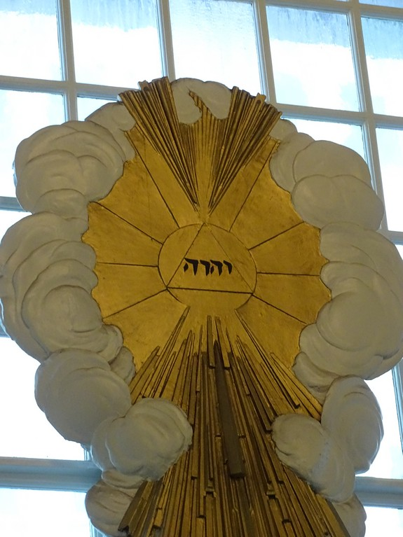 "The front of the 9/11 Church (St. Paul's Chapel) has a sculpture representing ""The Glory"" as God's holy name in Hebrew. The light coming from the Tetragrammaton inside of clouds represents the ""Glory"" described in Exodus 24:16-17 and Ezekiel 1:28."