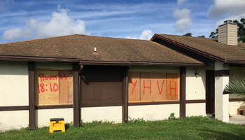 """Home in Florida boarded up against Hurricane Irma with """"YHVH"""" and """"Proverbs 18:10"""" written on it."""